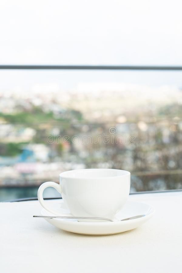 White ceramic cup with saucer on the table outdoor. On the background of the city royalty free stock photography