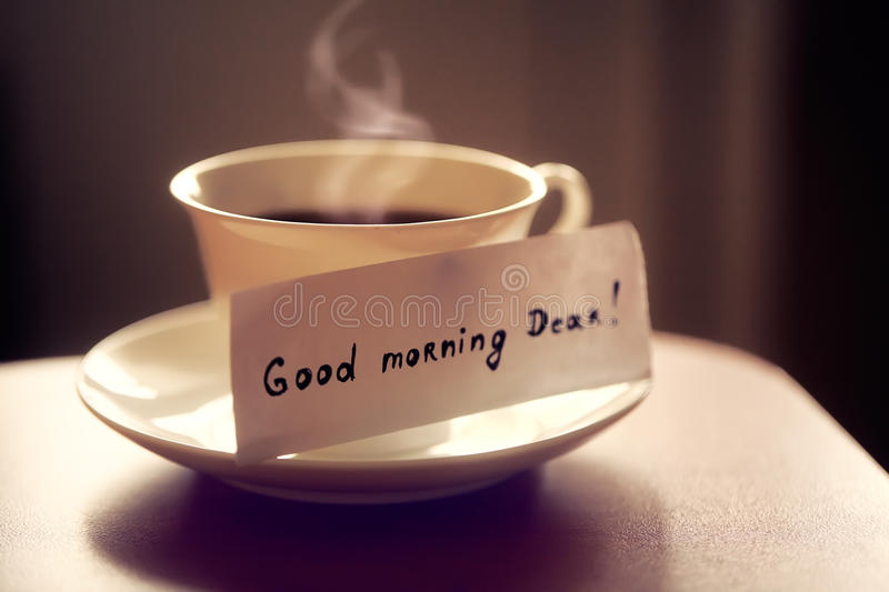 White ceramic cup of tea or coffee with nice letter `good morning dear` on kitchen table. Beautiful photo with breakfast stock image