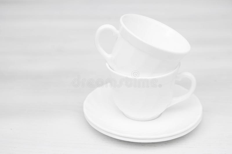 White ceramic cups with saucers on white table. Space for text royalty free stock photography