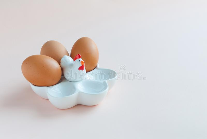 White ceramic egg holder with egg on pink background. Ceramic chicken royalty free stock photos