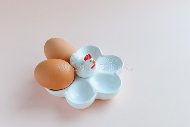 White ceramic egg holder with egg on pink background. Ceramic chicken stock images