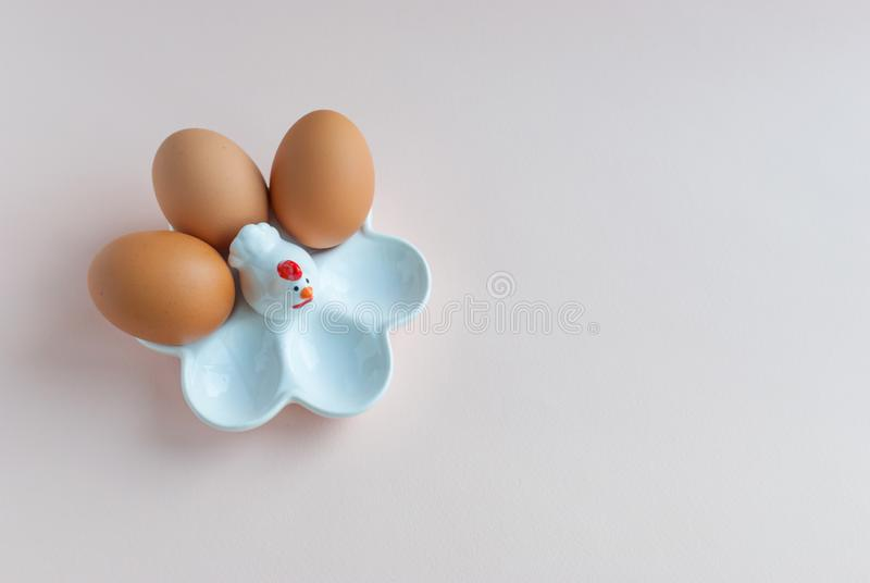 White ceramic egg holder with egg on pink soft background. Ceramic chicken. Top view stock photo