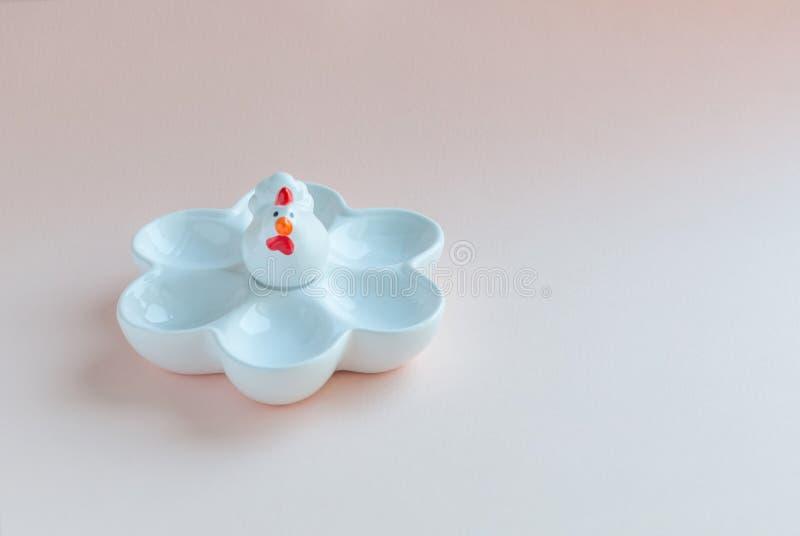 White ceramic eggcup on pink soft background. Ceramic chicken egg holder stock images