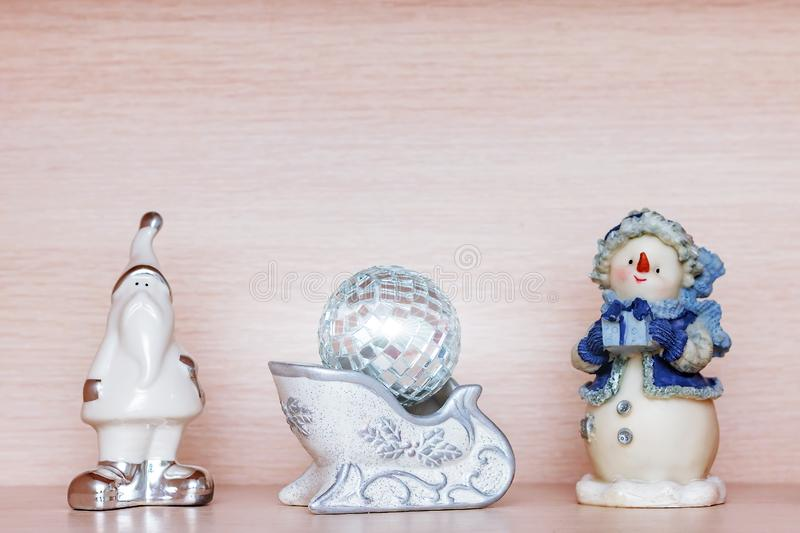 White ceramic figurine of santa claus, snowman in blue clothes and small disco xmas ball, copy space royalty free stock photos