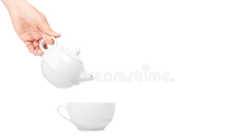 White ceramic kettle or teapot with cup in hand. Isolated on white background. copy space, template.  stock images