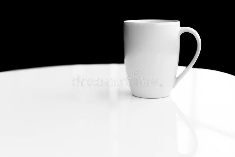White ceramic mug empty blank for coffee or tea. On white table royalty free stock images
