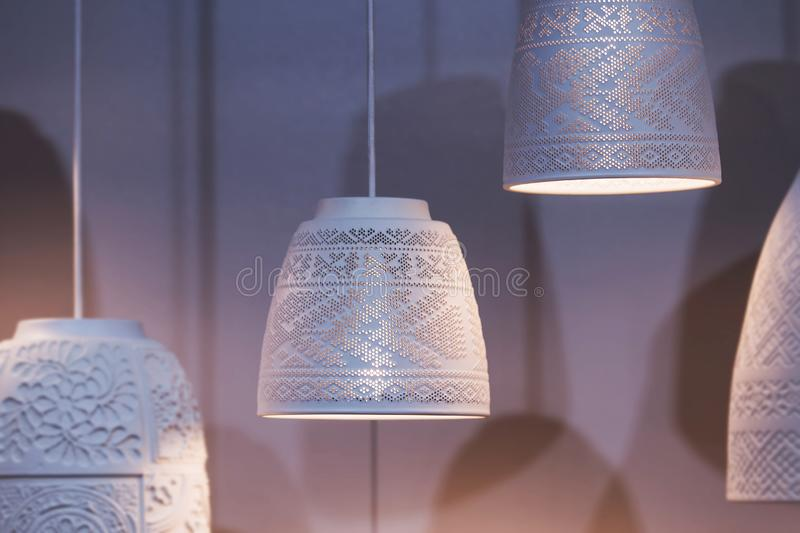 White ceramic pendant lights, chandeliers with ethnic patterns with a light bulb inside. Beautiful white lamps.  stock photography