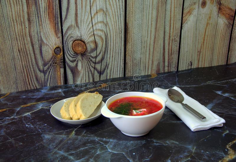 White ceramic plate with borsch, three slices of bread and a spoon on a napkin. Close-up. White ceramic plate with borsch, three slices of bread and a spoon on a royalty free stock photo