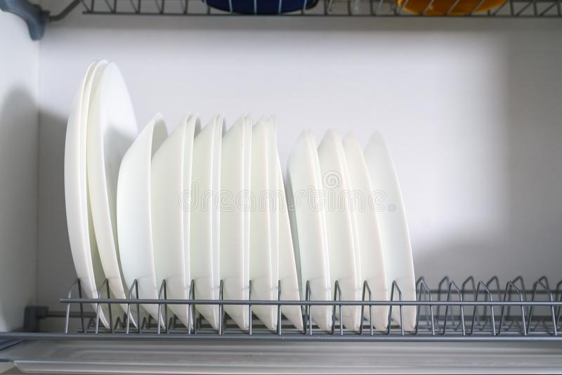 White ceramic plates stacked in a row in a drying locker close-up stock photos
