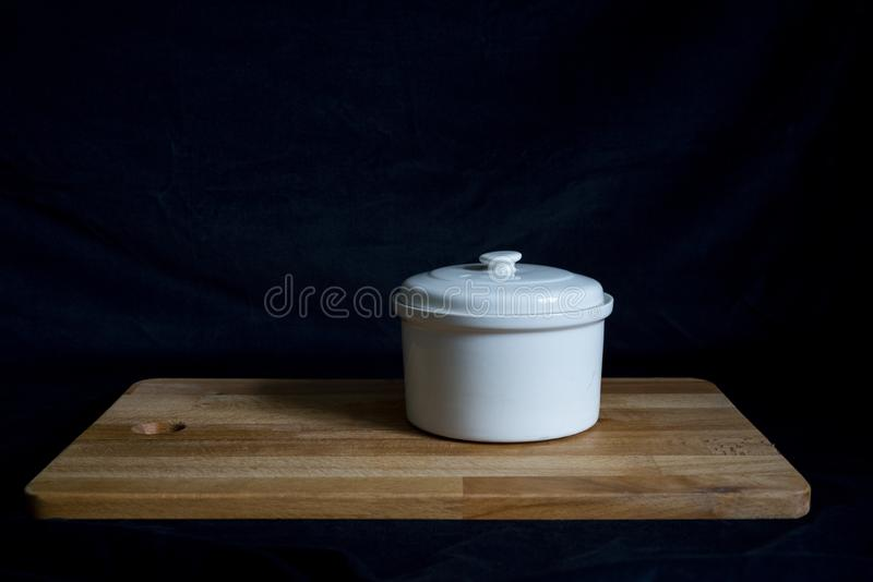 A white ceramic stew pot on a wooden board on the black background.  royalty free stock photo