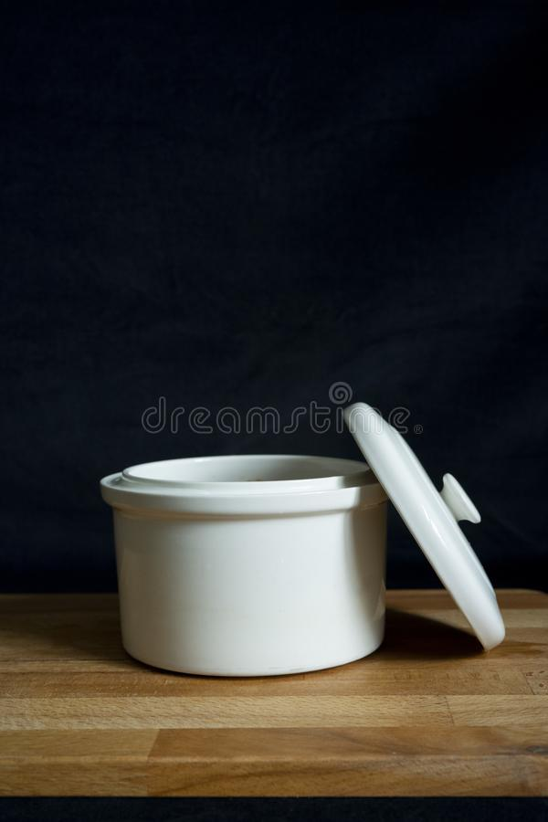 A white ceramic stew pot on a wooden board on the black background.  stock photography