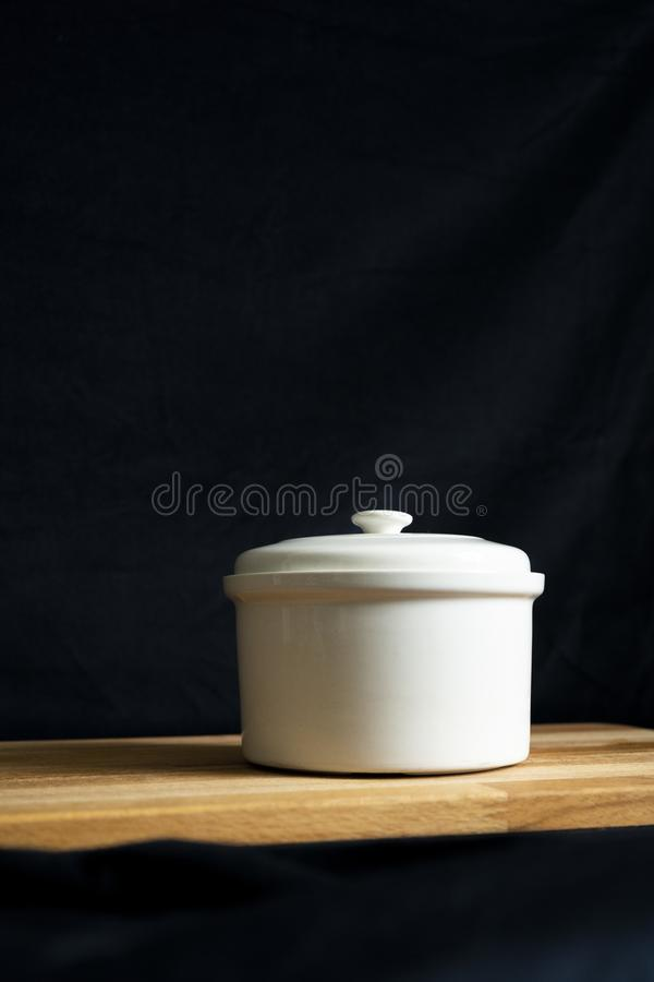 A white ceramic stew pot on a wooden board on a black background.  stock photo