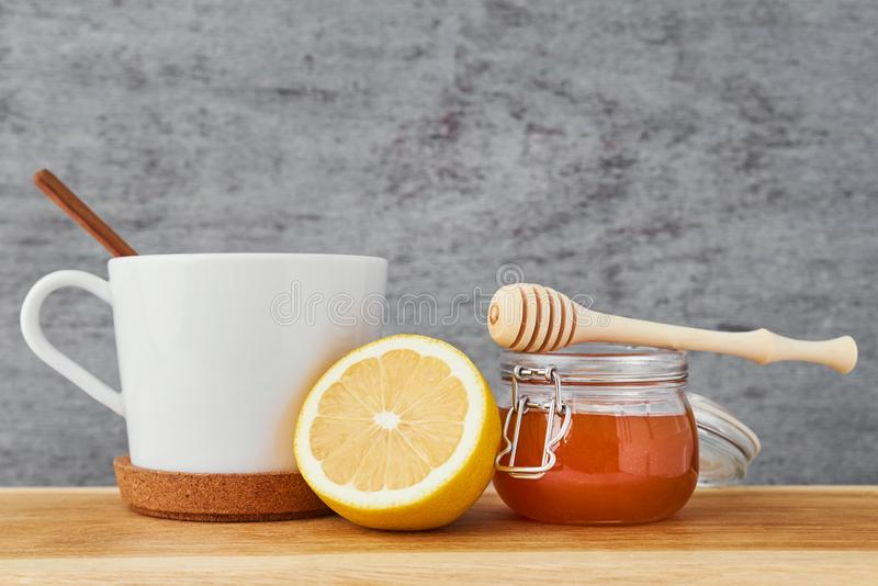 White ceramic teapot, lemon and honey in a glass jar close up royalty free stock photos