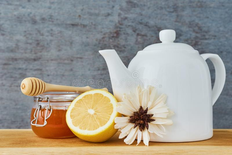 White ceramic teapot, lemon and honey in a glass jar close up royalty free stock images