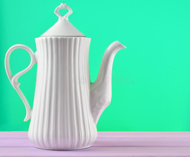 White ceramic teapot on a pastel purple wooden table isolated. On a yellow background stock images