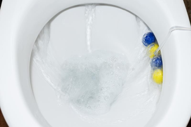 White ceramic toilet bowl with cleaning agent. Drain the toilet.  stock photography