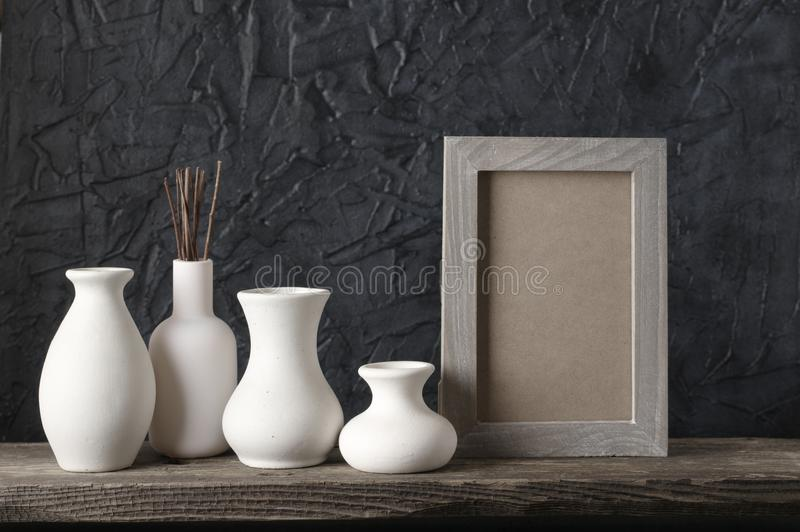 Neutral colored home decor. White ceramic vases and wood photoframe on distressed wooden shelf against rough plaster black wall. Home decor stock photo