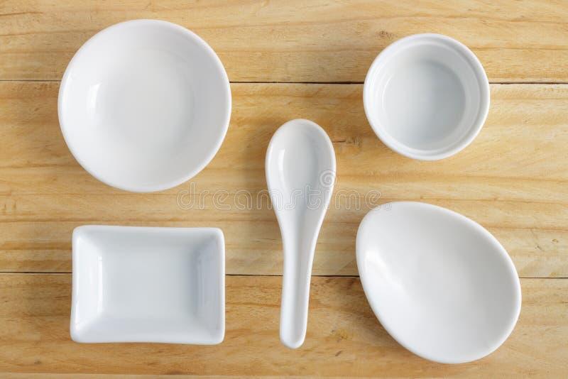 White ceramic ware on wooden table. White ceramic ware on wooden table, top view stock images