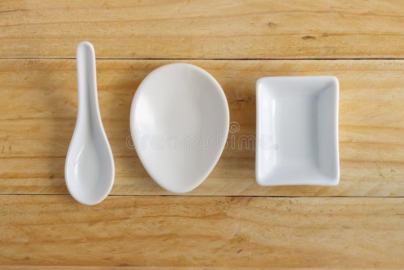 White ceramic ware on wooden table. White ceramic ware on wooden table, top view stock photo
