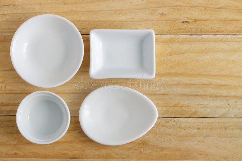 White ceramic ware on wooden table. White ceramic ware on wooden table, top view stock photos