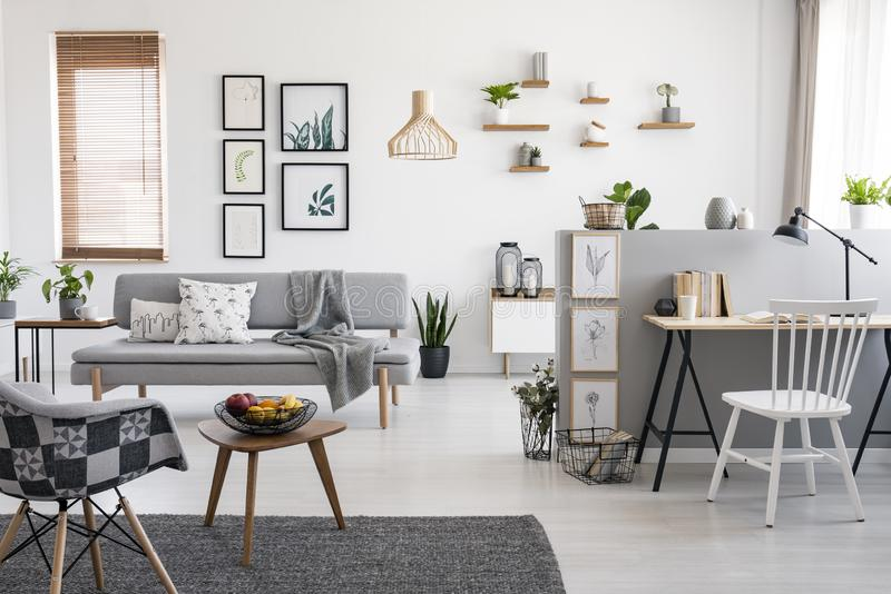 White chair at desk in spacious apartment interior with gallery above grey sofa near window. Real photo royalty free stock photo