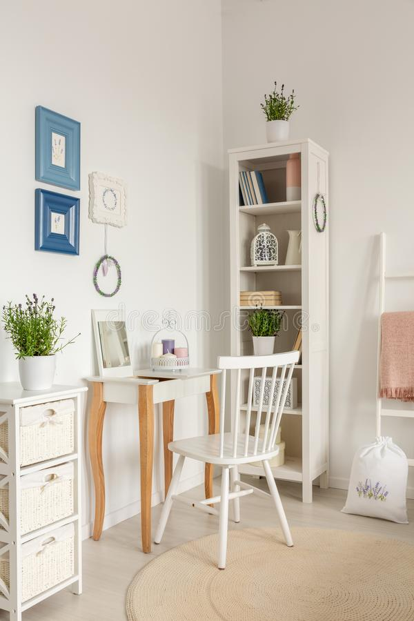 White chair at dressing table next to cabinet with plant in bedroom interior with posters. Real photo royalty free stock photo