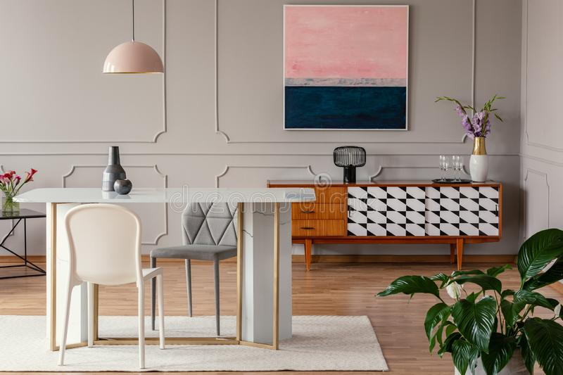 White chair and marble table under pink lamp in eclectic living room interior with painting above cabinet. Real photo stock photography
