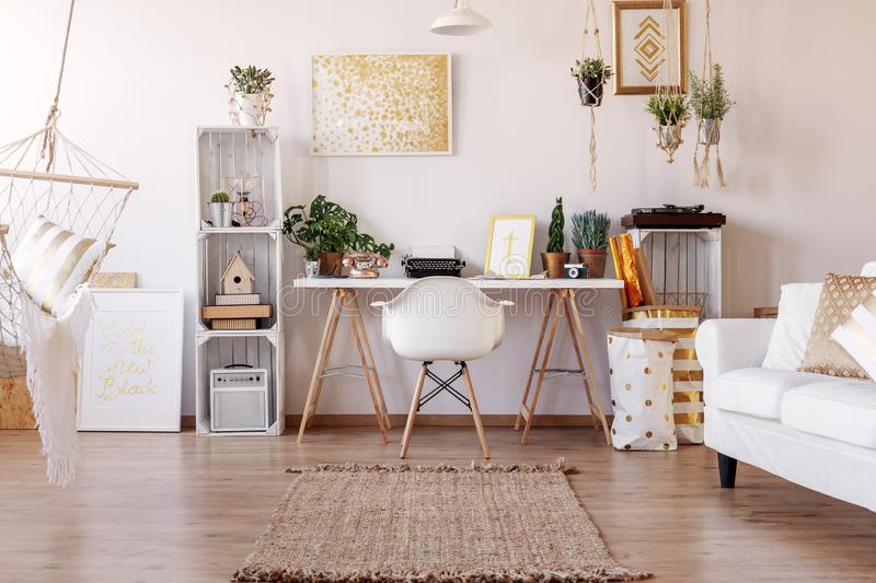 White chair placed by the desk with plants and typewriter in real photo of bright living room interior with posters and rug. White chair placed by the desk with royalty free stock photos