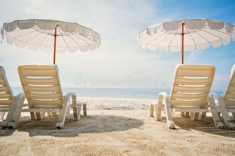 White chair with sun umbrella in the beach on seafront. Relax time on vacation royalty free stock image