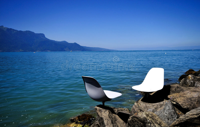 White chairs along the lake stock image