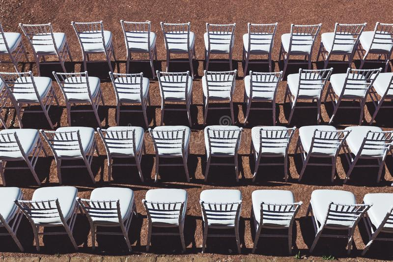 Rows of white chairs background on wedding ceremony. White chairs background on wedding ceremony outdoor royalty free stock images