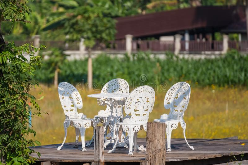 .White chairs with the bush Background in garden.Thailand royalty free stock images