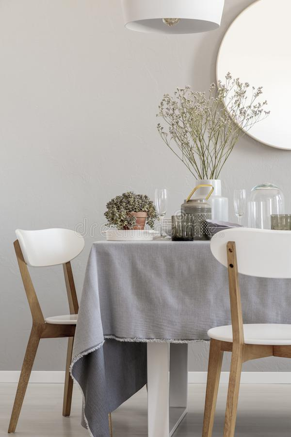 White chairs and laid table in an elegant and pastel dining room interior. Real photo. White chairs and table in an elegant and pastel dining room interior. Real royalty free stock image