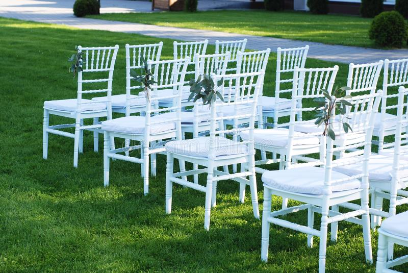 White Chairs at the Outdoor Wedding Ceremony Green Grass Background Party Celebrate Wedding Event. White Chairs at the Outdoor Wedding Ceremony Green Grass stock photo