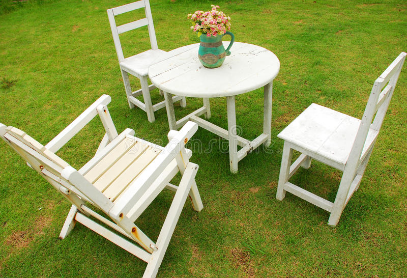 White chairs with round table. On green grass royalty free stock image