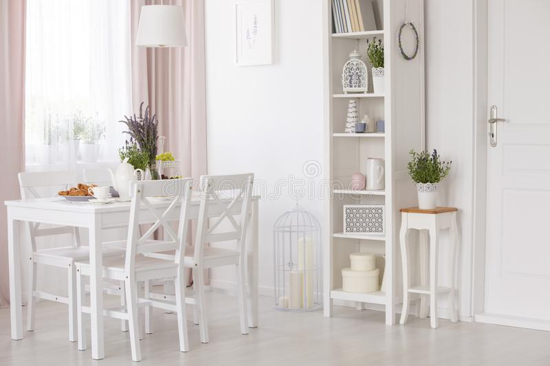 White chairs and table with flowers under lamp in dining room interior with lavender flowers. Real photo. Concept royalty free stock photo