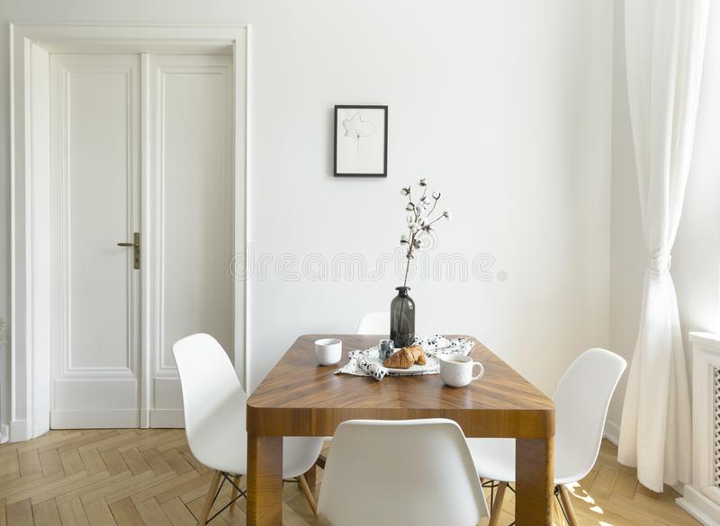 White chairs at wooden table in minimal dining room interior wit. H door and poster. Real photo royalty free stock photography