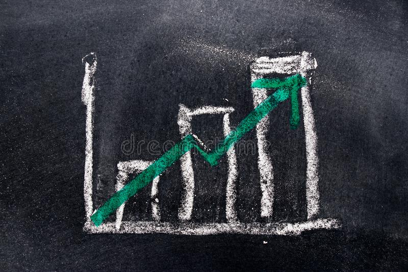 White chalk draw as bar chart and green chalk draw as upward. Arrow on black board background & x28;Concept for sale, profit, cost of company in uptrend& x29 stock image