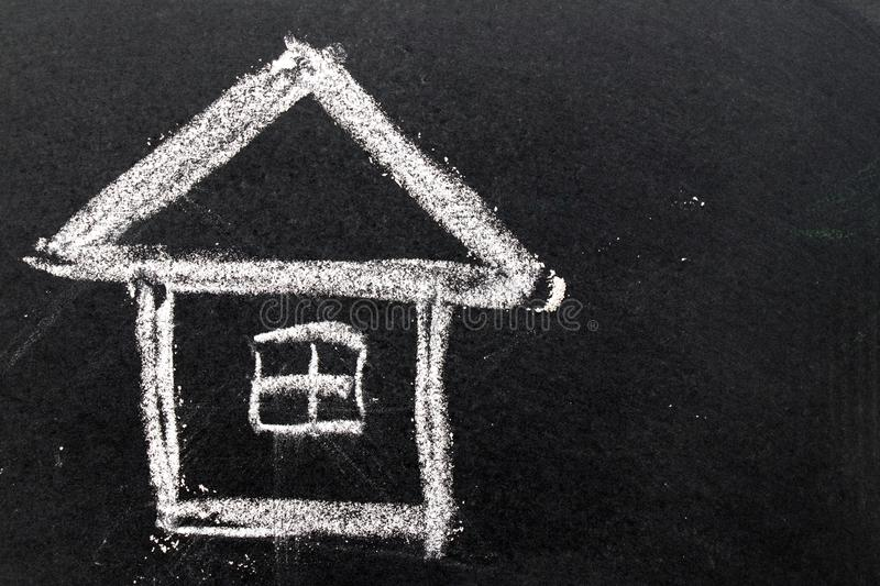 White chalk drawing as house shape on black board background. Concept of dream home, happy family royalty free stock image
