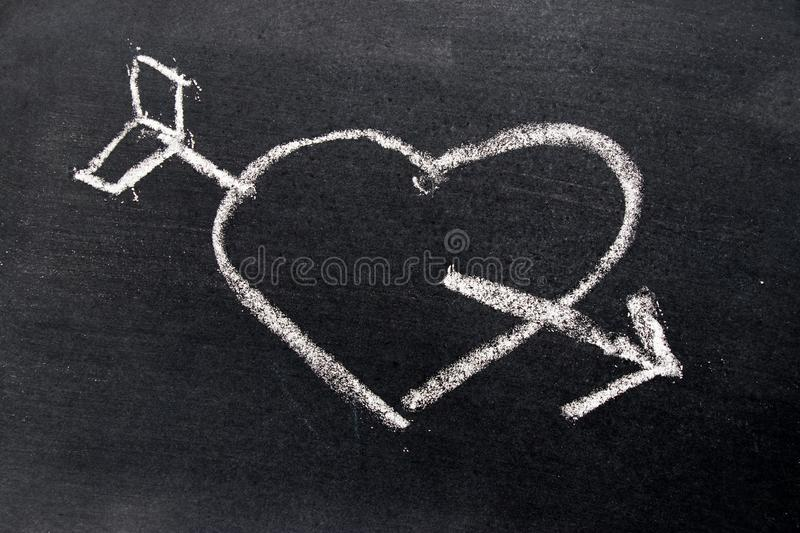 White chalk drawing in heart with arrow shape on black board stock photos