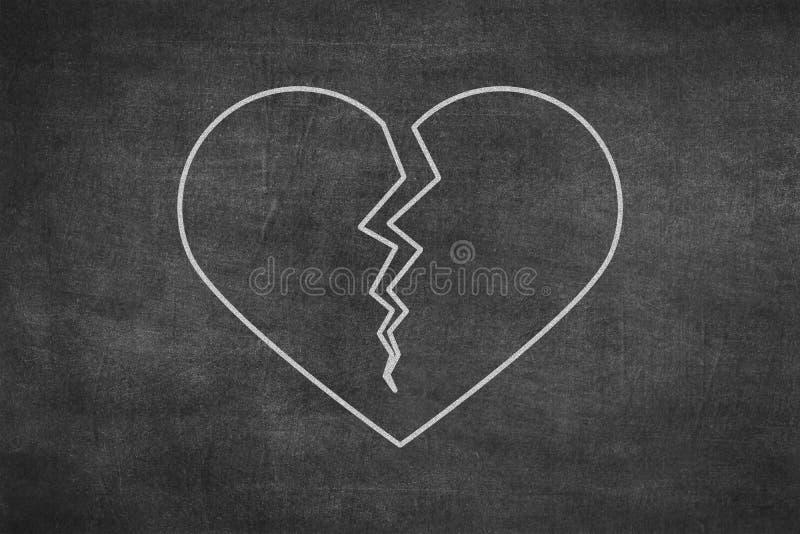 White chalk hand drawing in broken heart shape on blackboard royalty free stock photography