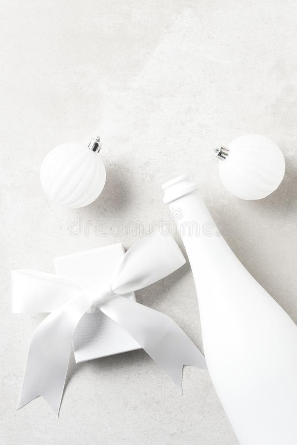 White Champagne bottle with white presents and Christmas Ornaments on a light gray table top. Flay lay with copy space stock photo