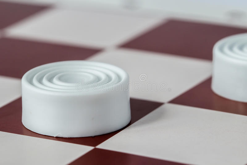 White checkers close-up on gaming board stock photography