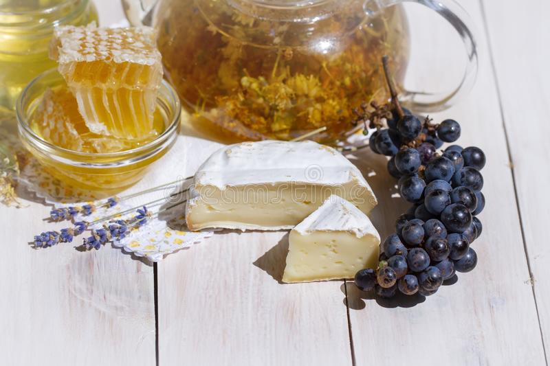 White cheese brie or camembert. Gourmet appetizer cheese plate with white cheese, honey, honeycomb, black grapes and royalty free stock photo