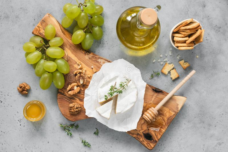 White cheese plate with crackers, honey, grapes stock images