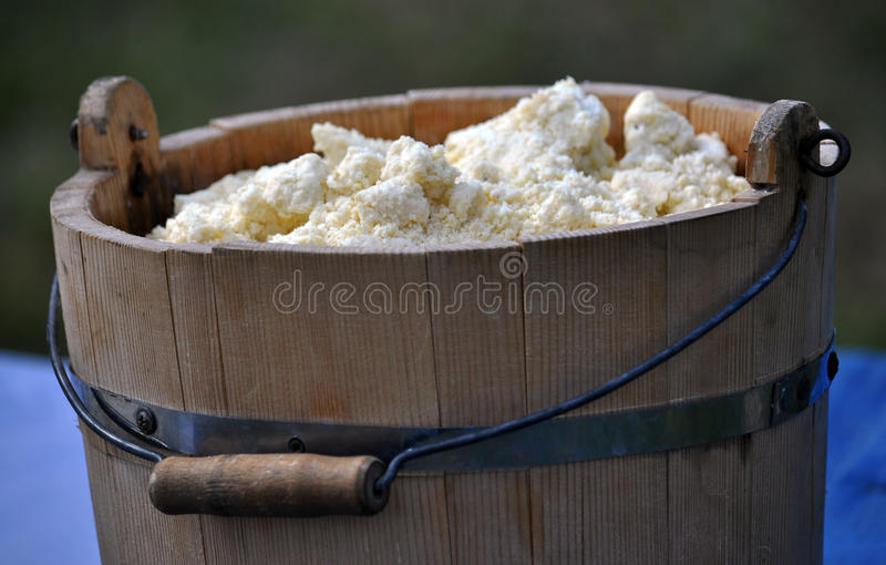 White cheese in a wooden tub_3. White cheese in a wooden tub with a handle. This valuable dairy product made from sheep's milk stock photography