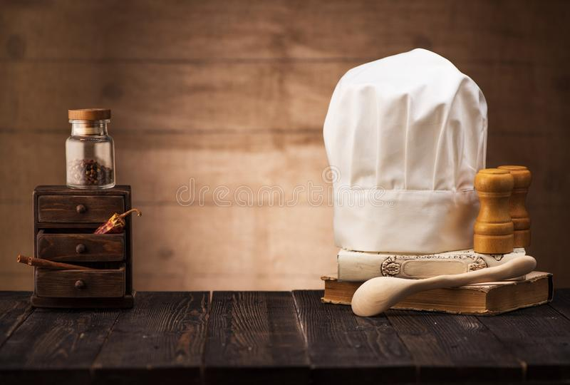 White chef`s hat and old cookbook on the kitchen table. Wooden spoon and spices. cooking concept stock image