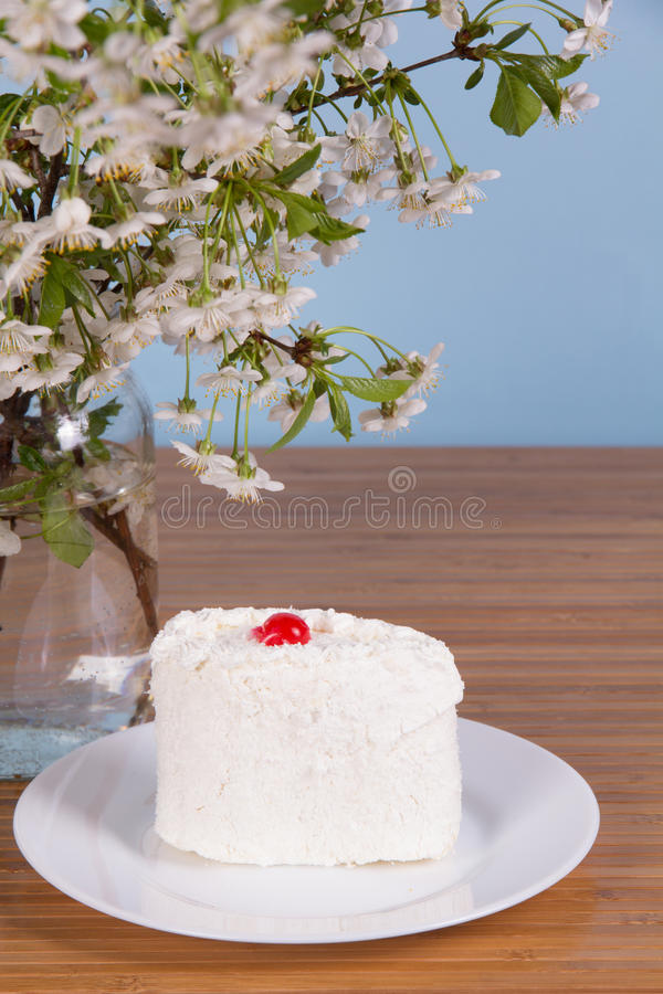 White cherry flowers and a cake on the table royalty free stock photos