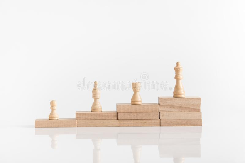 White chess pieces on a stepped stack of wooden blocks with queen piece stock photography