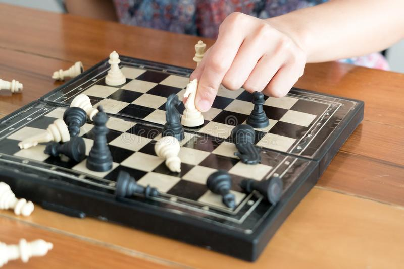 The white chess on women hand is fighting with black, think, discuss, committed, competition, winner, successful, dedicate concept royalty free stock photo